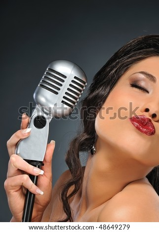 Portrait of a beautiful brunette singer with a retro microphone - stock photo