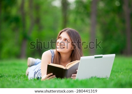 portrait of a beautiful brunette student girl with laptop computer and book on the green grass in the park in spring time. - stock photo