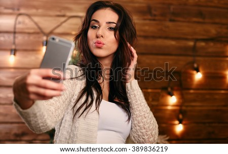 Portrait of a beautiful brunette taking a selfie with her smart phone at home - stock photo