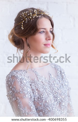 portrait of a beautiful brunette with a tiara in lace dress with pearls