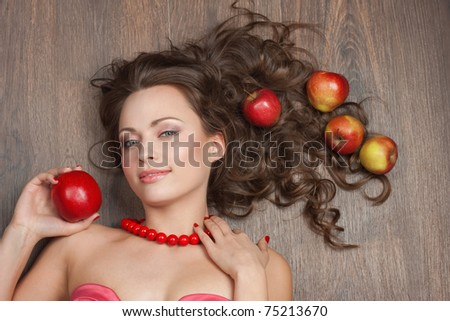 Portrait of a beautiful brunette with red apples - stock photo