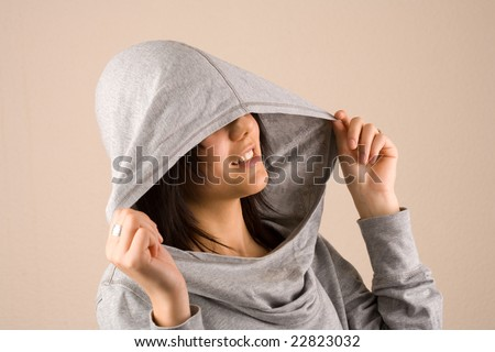 Portrait of a beautiful brunette with sweater and hood - stock photo