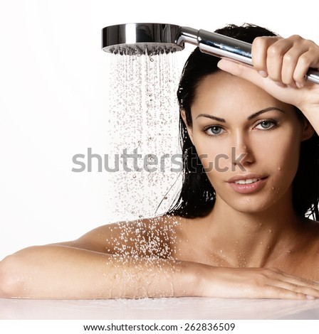 Portrait of a  beautiful brunette woman holds shower in hands  with falling water - stock photo
