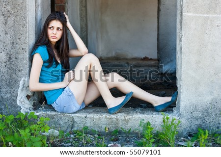 Portrait of a beautiful brunette woman in an industrial ruin
