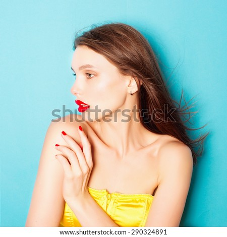 Portrait of a beautiful brunette woman in the studio on a blue background, the concept of beauty - stock photo