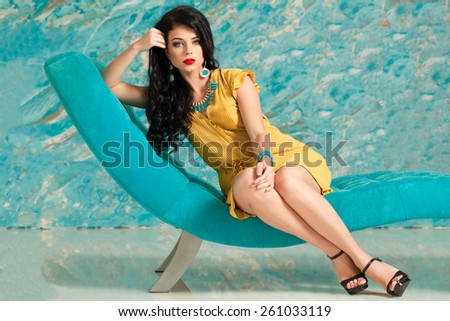 Portrait of a beautiful brunette woman with long hair relaxing on modern chair - stock photo