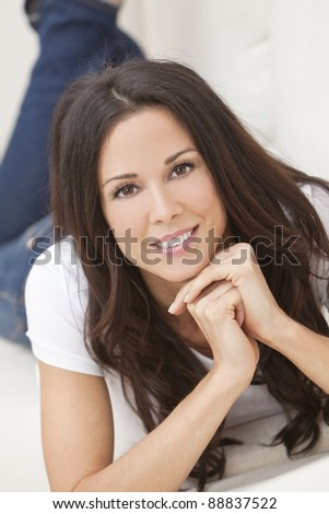 Portrait of a beautiful brunette young woman in jeans and t-shirt smiling laying on her sofa at home