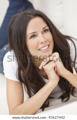 Portrait of a beautiful brunette young woman in jeans and t-shirt smiling laying on her sofa at home - stock photo