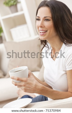 Portrait of a beautiful brunette young woman in jeans and t-shirt smiling siting on her sofa at home drinking a cup of tea or coffee