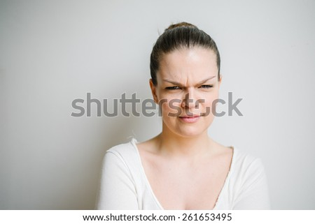 Portrait of a beautiful brunette young woman with doubtful face, white background - stock photo
