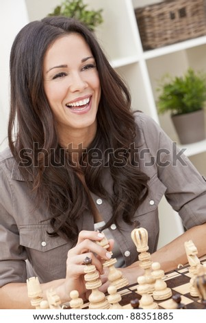 Portrait of a beautiful brunette young woman with perfect teeth smiling and laughing whilst playing chess - stock photo