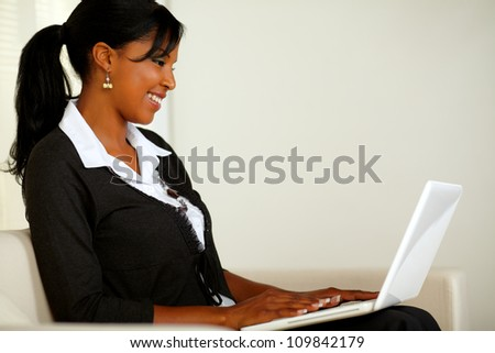 Portrait of a beautiful business black woman reading on laptop while sitting on couch - stock photo
