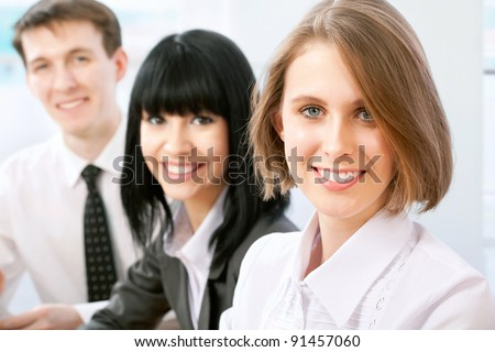 Portrait of a beautiful business woman at a meeting with colleagues in the background. - stock photo