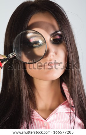 Portrait of a beautiful business woman holding a magnifying glass. - stock photo