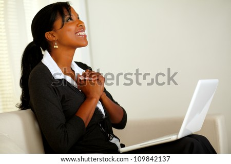 Portrait of a beautiful business woman on black suit smiling and looking up and thanking while sitting on sofa at home indoor