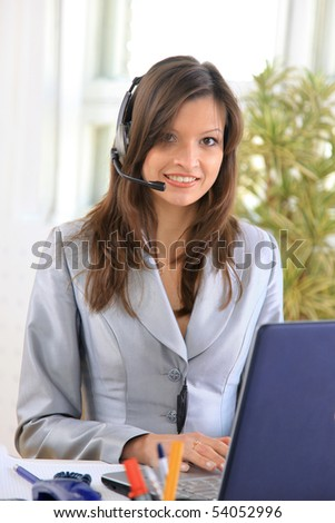 Portrait of a beautiful business woman working at her desk with a headset and laptop - stock photo