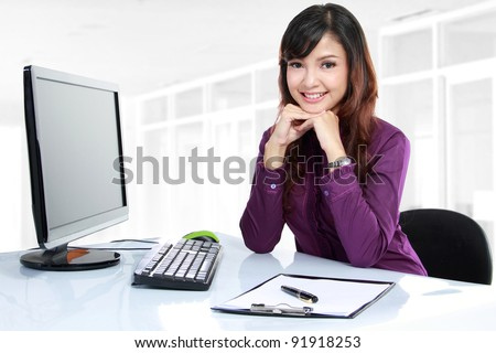 Portrait of a beautiful business woman working on her desk in an office environment. - stock photo