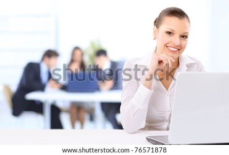 Portrait of a beautiful business woman working on her laptop in an office environment. Colleagues in the background - stock photo