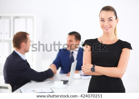 Portrait of a beautiful businesswoman standing in office with colleagues