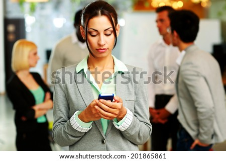 Portrait of a beautiful businesswoman using smartphone in front of colleagues - stock photo
