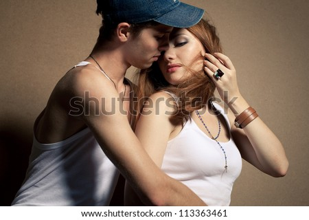 portrait of a beautiful casual couple in jeans sitting together over wooden background. boy hugging girl and kissing. studio shot - stock photo
