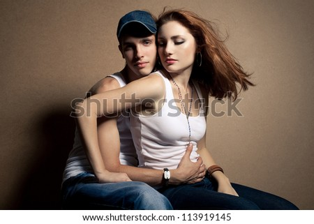 portrait of a beautiful casual couple in jeans sitting together over wooden background. boy hugging girl with flying hair. studio shot - stock photo