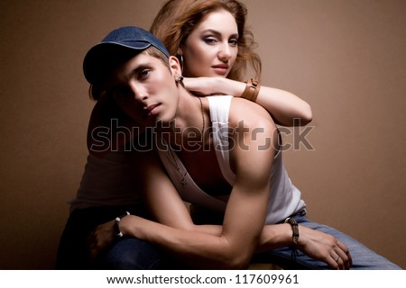 portrait of a beautiful casual couple in jeans sitting together over wooden background. studio shot