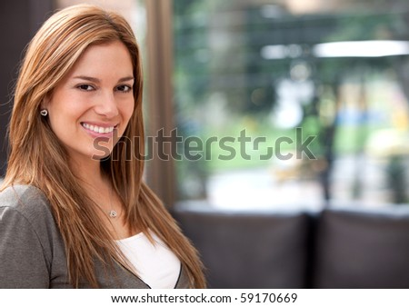 Portrait of a beautiful casual woman smiling at home - stock photo