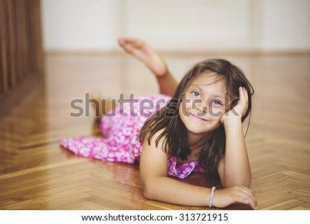 portrait of a beautiful Caucasian girl laying on the floor, posing for camera. cute expression on her face, peaceful and satisfied school girl - stock photo