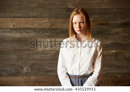 Portrait of a beautiful Caucasian woman looking seriously at camera. Blond girl well-dressed in white shirt, showing neutral emotions as if waiting for somebody to speak. Stylish office look. - stock photo