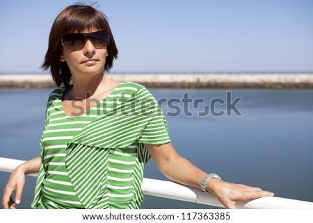 Portrait of a beautiful caucasian woman standing near the sea - stock photo