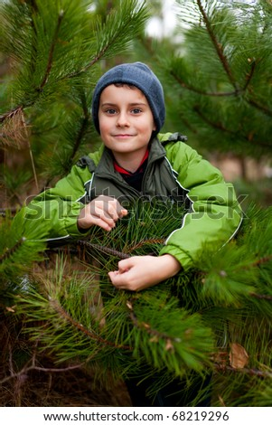 Portrait of a beautiful child outdoor, among pine branches - stock photo