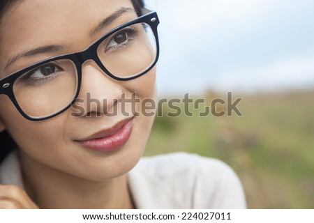 Portrait of a beautiful chinese asian girl or young woman outside wearing glasses - stock photo
