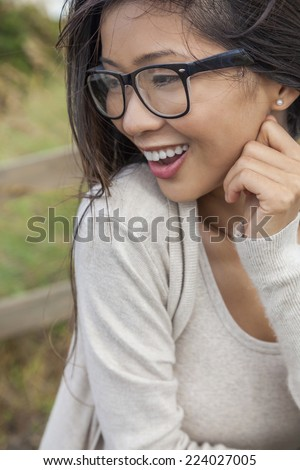 Portrait of a beautiful Chinese Asian girl or young woman outside wearing glasses happy and laughing - stock photo