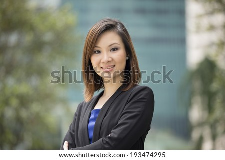 Portrait of a beautiful Chinese businesswoman in smart business suit. Asian business woman standing outside in modern city. - stock photo
