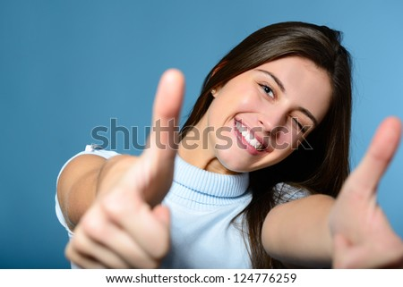Portrait of a beautiful, confident and cheerful teenager girl showing thumbs up isolated on blue - stock photo