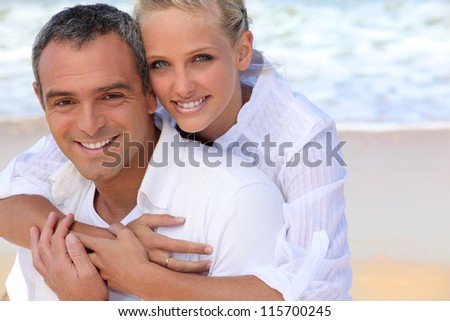 Portrait of a beautiful couple at the beach - stock photo