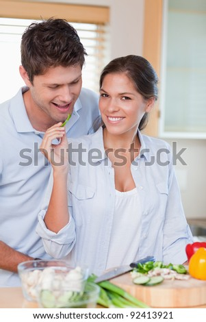 Portrait of a beautiful couple cooking in their kitchen - stock photo