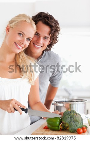 Portrait of a beautiful couple cooking while looking at the camera - stock photo