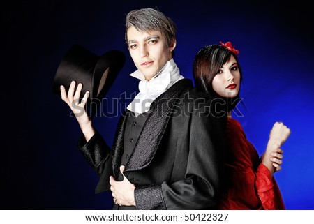 Portrait of a beautiful couple in medieval costumes with vampire style make-up. Shot in a studio. - stock photo