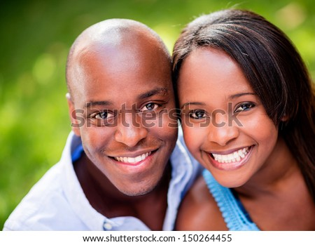 Portrait of a beautiful couple smiing outdoors  - stock photo