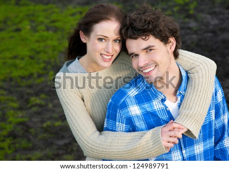 Portrait of a beautiful couple smiling outdoors - stock photo
