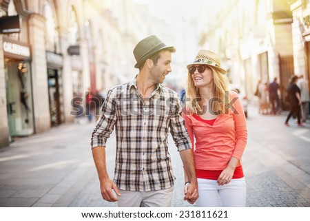 portrait of a beautiful couple walking in the street in summer, they wear hats and sunglasses for the woman - stock photo