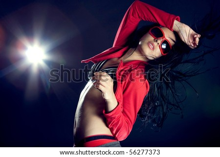 Portrait of a beautiful dancing girl on dark background - stock photo