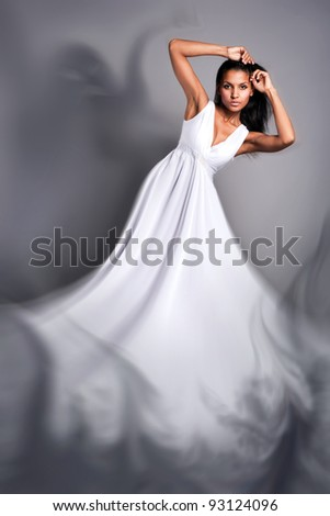 portrait of a beautiful dark-skinned woman in a white dress in the studio - stock photo