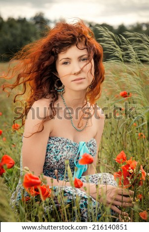 Portrait of a beautiful dreamy girl sitting in the poppies field with bouquet in hands - stock photo