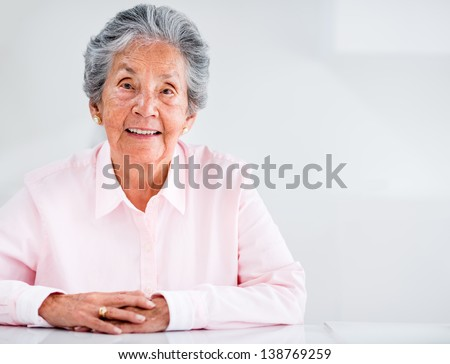Portrait of a beautiful elder woman at home smiling - stock photo