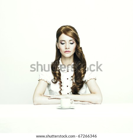 Portrait of a beautiful elegant lady at white table - stock photo