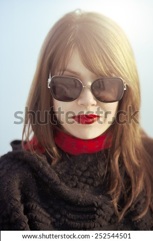 Portrait of a beautiful elegant young woman with dark sunglasses and red lipstick. - stock photo