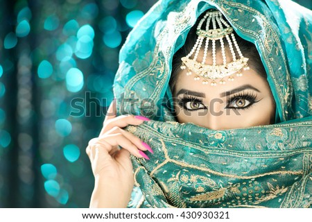 Portrait of a beautiful ethnic indian asian woman in pretty makeup and jewellery - stock photo